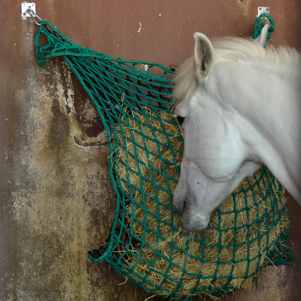 caballo comiendo de red para heno slow feeding de portoverde